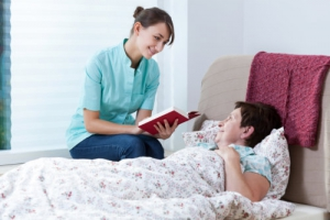 caregiver reading a book to her elderly patient who is sick